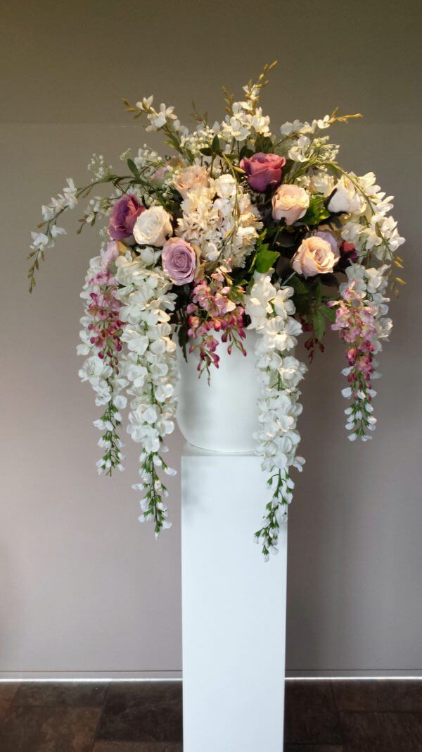 Bloemstuk bruiloft op witte zuil